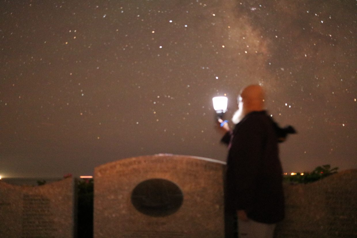 Bill holding a light toward the stars